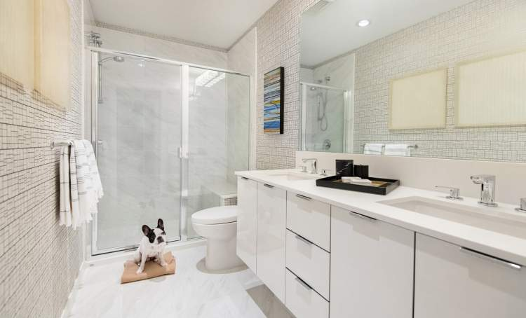 En suite bathrooms have spa-inspired details, like polished engineered stone countertops, oversized vanity mirrors, and custom flat-panel cabinets.