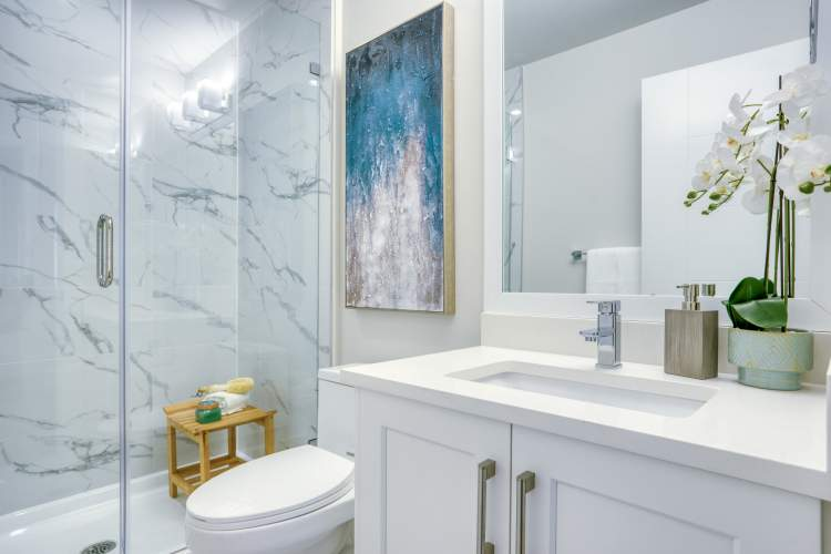 Main bathrooms feature a bathtub with 1x2 foot ceramic tile surround, quartz countertop and vanity lighting.