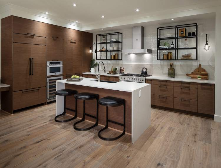 Modern, open-plan kitchens feature abundant storage concealed inside shaker-style cabinets with warm wood accents. Deep, farmhouse sinks and exposed shelving add character.
