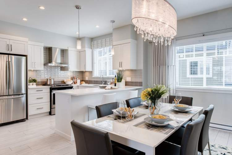 The contemporary kitchen is the heart of your home, equipped with a Whirlpool professional gas range, rich quartz countertops and an over-sized kitchen island .