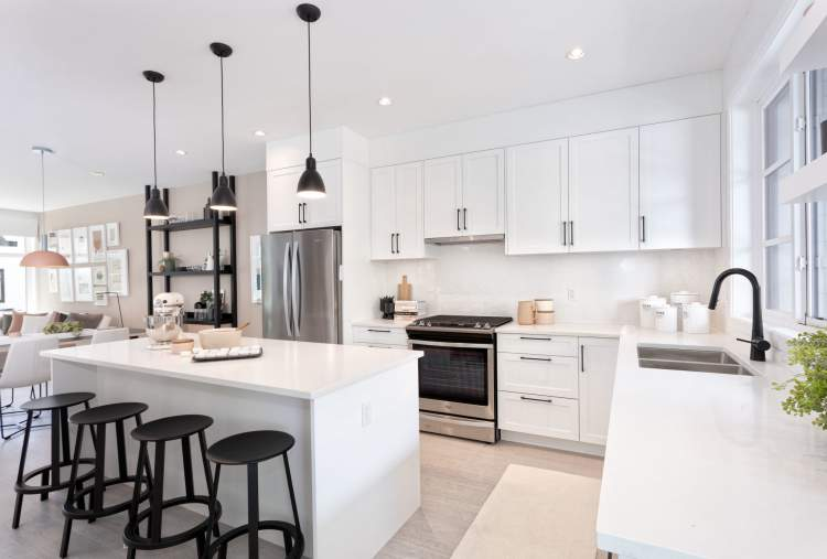 Kitchens feature Shaker cabinetry, polished quartz countertops, and Whirlpool stainless steel appliances.