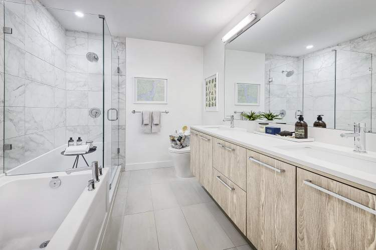 Luxurious Bathrooms feature stone countertops, 9' shower/tub combo with frameless glass enclosure, large double-sink vanity.