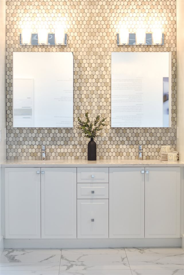 En suites feature double vanities with Caesarstone quartz countertops and an elegant tiled wall.