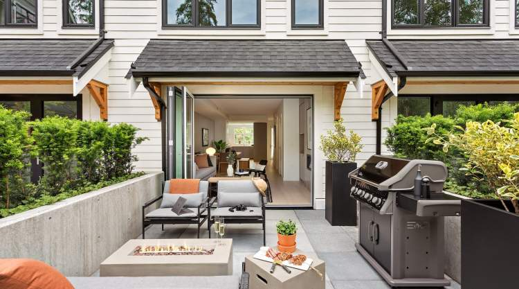 Accordion-style doors transition to a secluded riverside patio.
