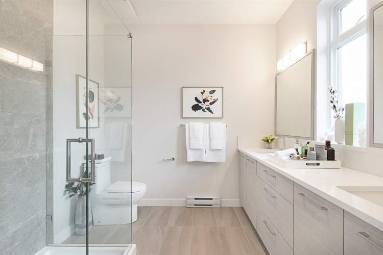 Shaker-style cabinetry, porcelain tiles, double sinks, quartz countertops, and frameless glass showers with rain shower heads.