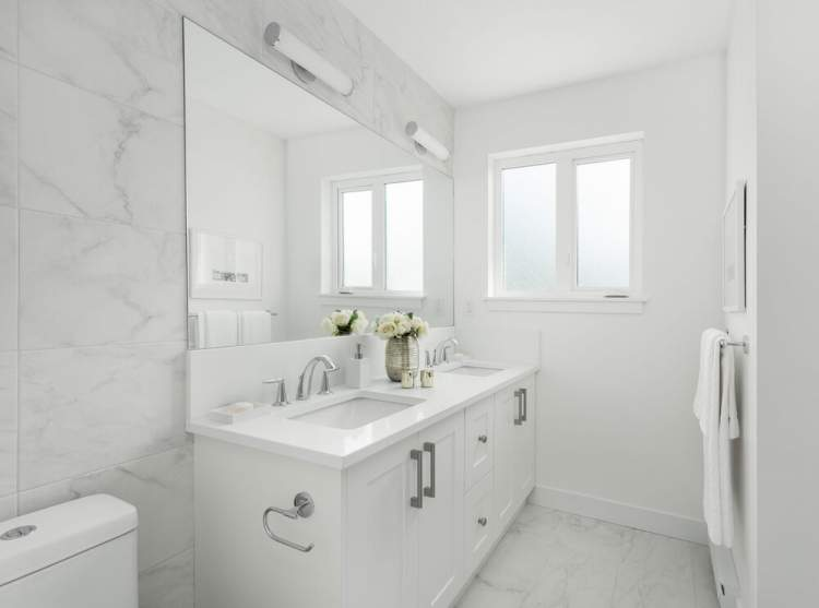 Main bathrooms feature a relaxing bathtub, quartz countertops, and sophisticated vanity lighting.