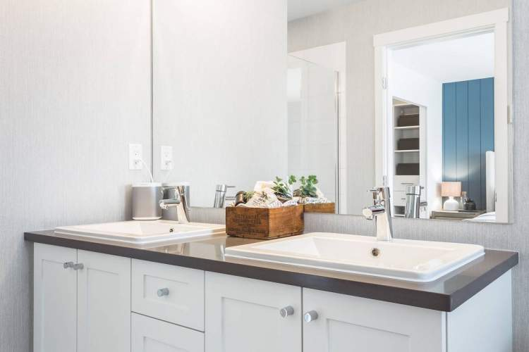 Double sinks with floating vanity, contemporary cabinetry, and imported quartz countertops make bathrooms beautiful.