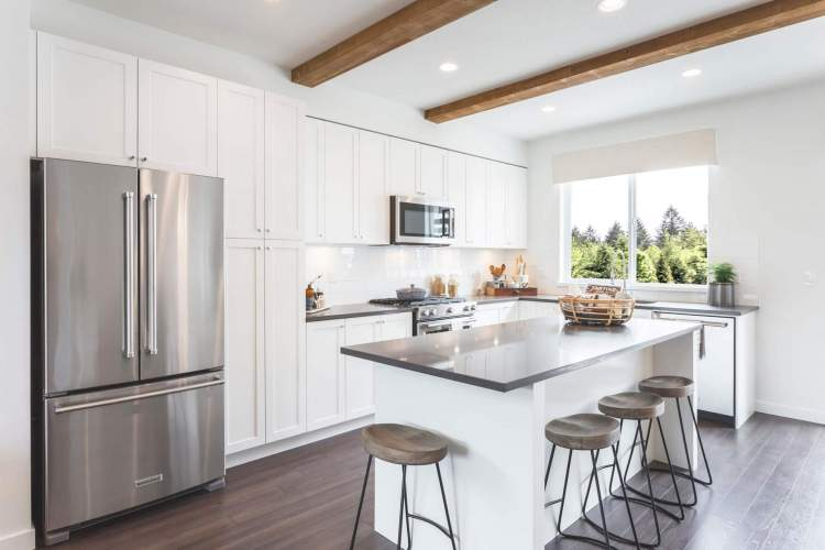 Spacious kitchens include open islands, imported quartz countertops, and stainless steel appliances.