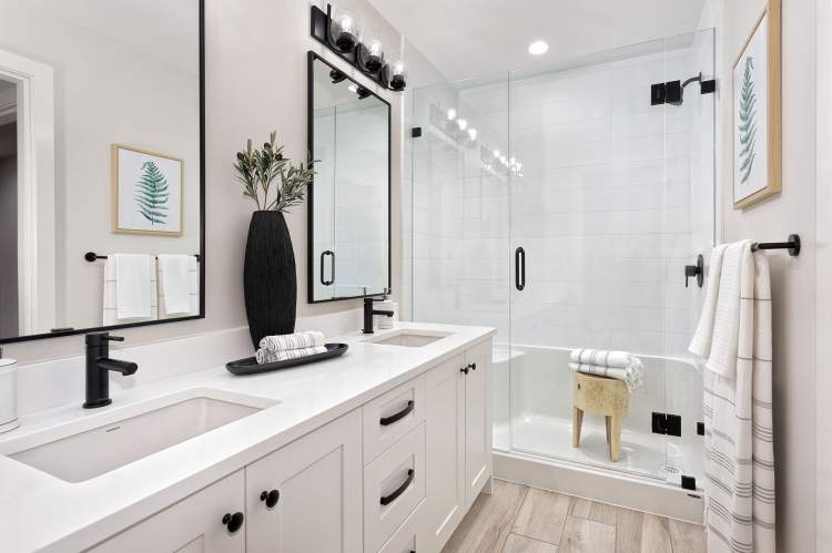 En suite with dual vanities, Shaker-style cabinetry, and frameless glass-enclosed shower.