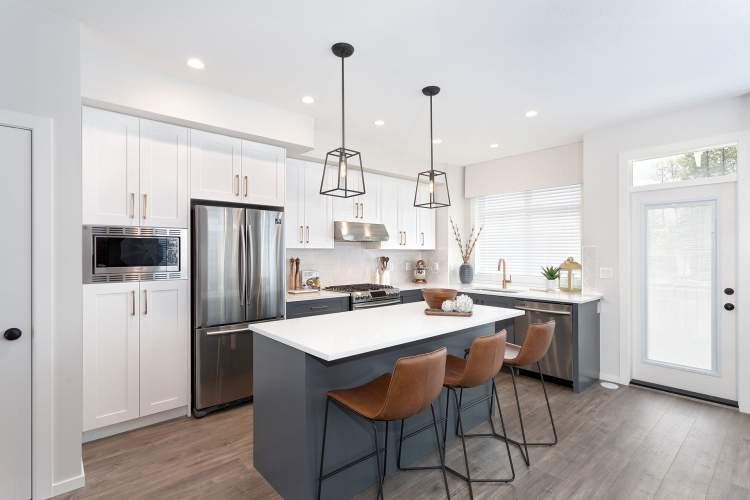 Full-height, Shaker-style cabinetry with quartz countertops and stainless steel appliances.