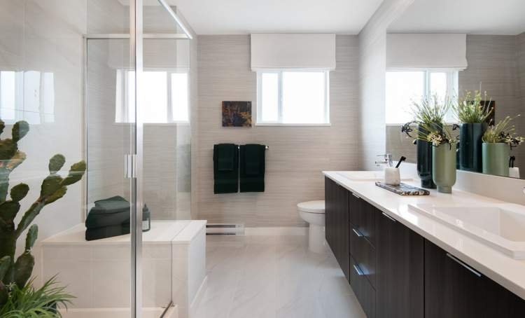 Spa-inspired en suite complete with integrated bench seating and a handheld wand.