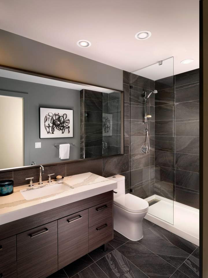 Large-format tile flooring with floor-to-ceiling shower surrounds and minimalist fixtures.
