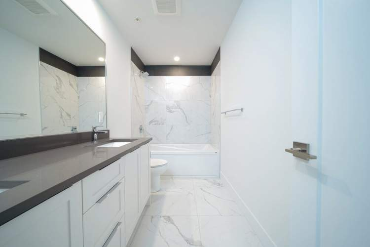 Spacious 4' walk-in frameless shower finished with floor-to-ceiling marbled tile.