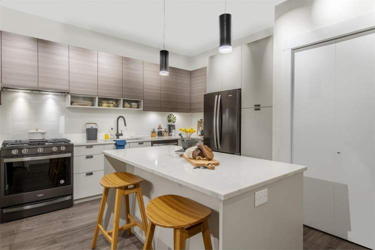 Equipped with gas ranges to complement the quartz countertop islands and a Whirlpool appliance package.