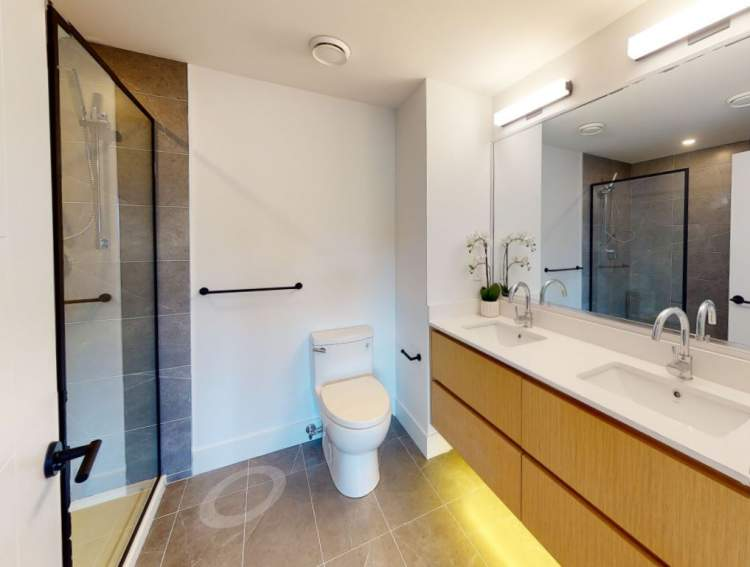 Spa-inspired en suite with glass shower and soft grey porcelain tile.